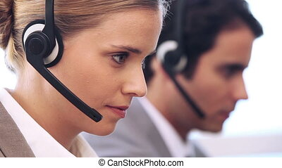 Call centre agent working with a headset in an office