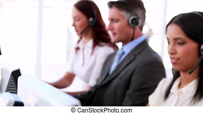 Call centre agents working and talking on headsets in the...