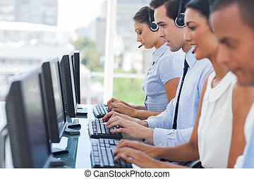 Call centre employees working on computers with their...