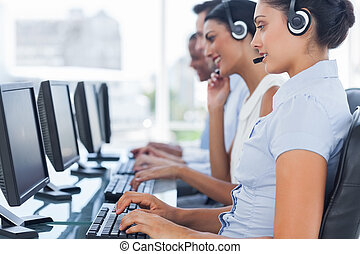 Call centre workers sitting in line while helping people on...