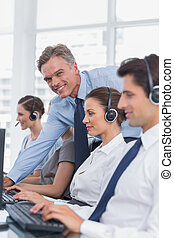 Call centre working with headset in a bright office
