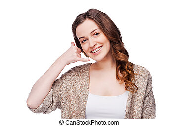 Call me! Beautiful young smiling woman looking at camera and gesturing mobile phone near ear while standing isolated on white