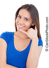 Call me! Beautiful young smiling woman looking at camera and gesturing while standing isolated on white