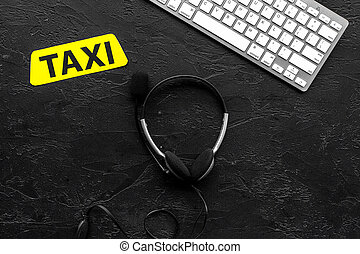 Call taxi online. Taxi label, keyboard, headphones on black background top view