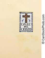 SAN JUAN, PUERTO RICO - MARCH 14, 2015: Historic, tiled sign identifies the street and shows the symbol of a cross. The wall is pale yellow, as banana flesh.