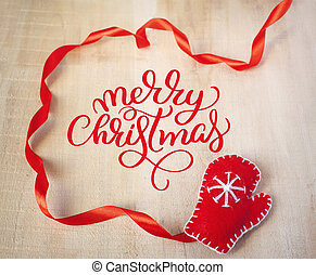 Calligraphy Text Merry Christmas, with Santa Claus red mitten on a wooden background. Flat lay, top view photo mockup