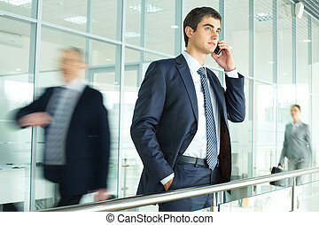 Calling - Businessman standing by banisters and calling with...