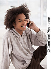 Calling friends. Cheerful African teenager talking on the mobile phone and smiling