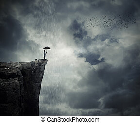 Man with an umbrella stand on the edge of the cliff, calling the rain. Mysterious place above the clouds.