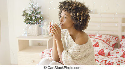 Calm adult in sweater sipping tea while in bed - Single...