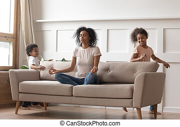 Calm african mom doing yoga on sofa relaxing with kids