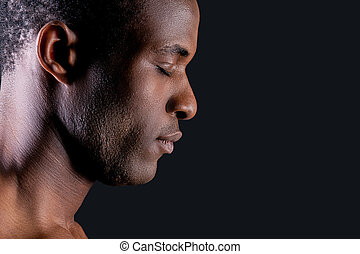 Calm and confident. Side view of young African man keeping eyes closed while standing against grey background