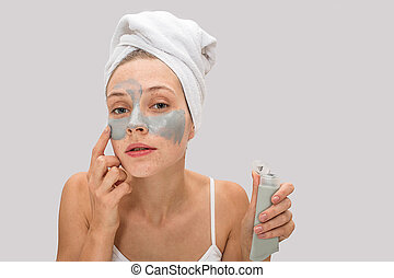 Calm and peaceful freckled woman looks closer to camera and touches her face. She puts on some mask on cheeks and skin zone underneath eyes. Model has tube of mask. Isolated on grey background.