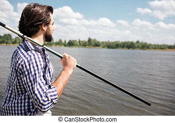 Calm and thoughtful guy is standing at the edge of lake and looking at it. He is holding fish-rod on his right shoulder with right hand. There is a beautiful weather outisde.