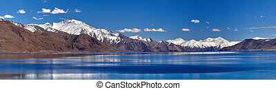 Calm autumn on Lake Pangong, blue water, brown mountains with snow on peaks, photo panorama, Jammu and Kashmir, India.