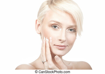 calm beauty portrait of a young woman putting cream