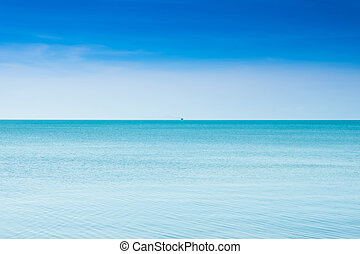Calm blue sea with a boat at boundlessly of sea.