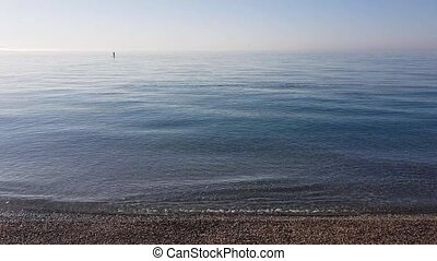 Calm blue surface of the waves and the quiet of the beach of...