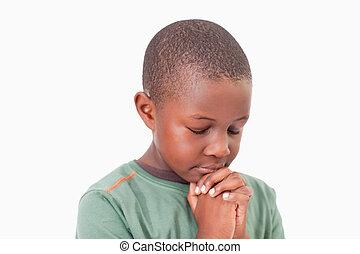 Calm boy praying against a white background