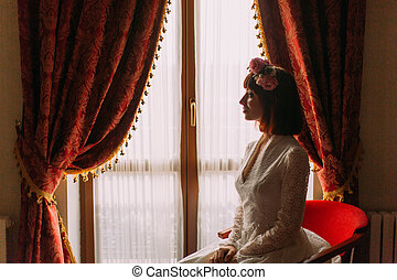 Calm bride sitting near window in bedroom, woman have final preparation for wedding, waiting groom.