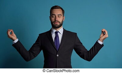 Calm businessman in campaign suit relaxing, meditating. Handsome european man calms down, breathes deeply with mudra om. Slow motion. Studio footage.