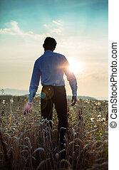 Calm businessman walking towards the sunset