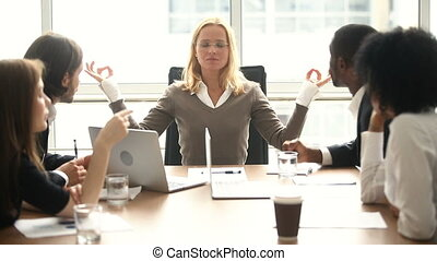 Calm businesswoman meditating at meeting with multiracial colleagues, no stress