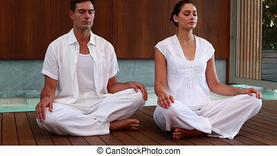 Calm couple in white sitting in lotus pose at the health spa