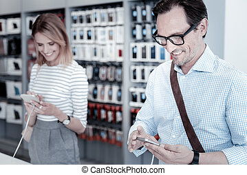 Calm customers testing devices in a shop