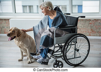Calm disabled woman petting the hound at home