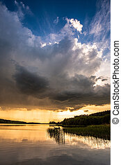 Calm dusk at the summer lake with dynamic clouds