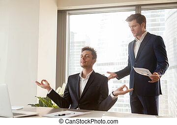 Calm employee meditating at workplace, angry boss shouting,...