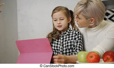 Woman spending free time with little girl and using digital...