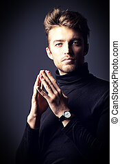 calm face - Modern handsome young man in black pullover ...