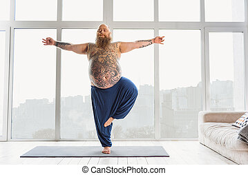 Relaxed bearded thick guy is doing yoga at home. He is standing on one leg and stretching arms sideways. His eyes are closed with tranquility