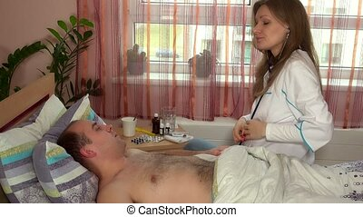 Calm female doctor listening male man with hairy breast by...