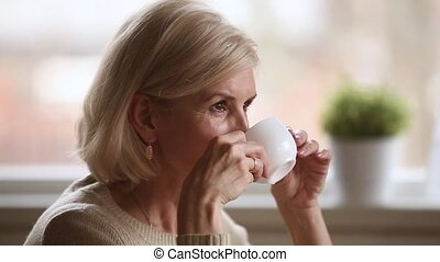 Calm happy old woman sitting alone holding cup enjoying...