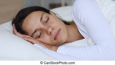 Calm healthy young woman serene face sleeping well in comfortable bed lying on soft pillow orthopedic mattress, peaceful lady resting in good night sleep concept on white linen sheets in bedroom