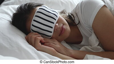 Calm healthy young woman wear sleeping mask resting in comfortable bed lying on soft pillow orthopedic mattress enjoying peaceful serene good night sleep on white linen sheets in bedroom concept