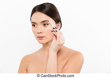Calm lady removing make up with cotton stick and looking aside