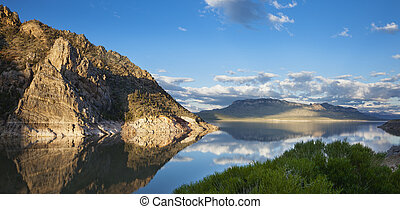 Calm lake in the American West reflecting a rocky point