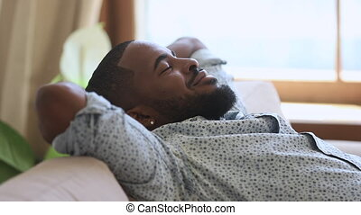 Calm relaxed lazy african american young man resting napping on sofa with eyes closed at home, happy healthy guy breathing fresh air lounge on couch hands behind head enjoy stress free peaceful day