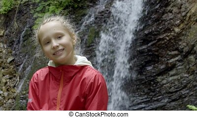 Calm little girl looking at camera in forest