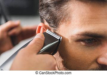 Calm man getting haircut by machine