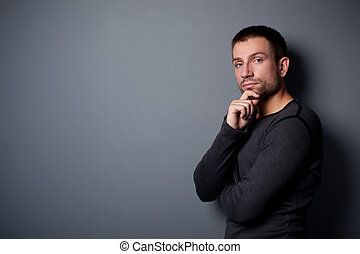 Calm man standing against the wall - Portrait of young ...