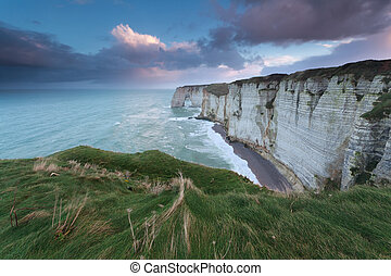 calm marine sunrise over cliffs in ocean