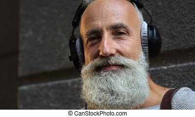Calm mature guy with headphones looking into camera - Music...