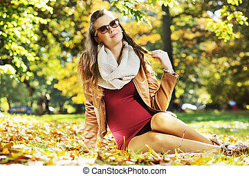 Calm mother lying on the autumn leaves