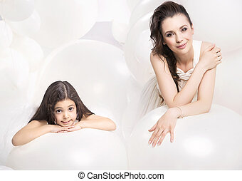 Calm mother relaxing with a cute daughter