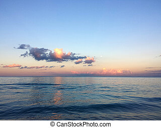Calm ocean waters of Waimanalo Bay at dusk with clouds and...